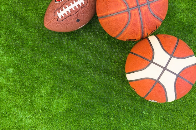 An overhead view of basketball and rugby ball on green turf