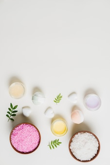 An overhead view of bath bomb; cream and salt on white backdrop