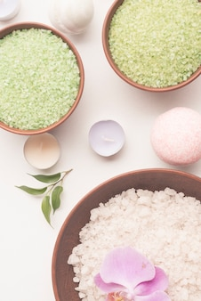 Overhead view of bath salt bowls with candle and spa bomb on white background