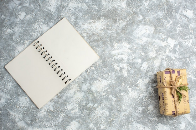 Vista dall'alto di un bellissimo regalo natalizio con iscrizione d'amore su un taccuino aperto sul tavolo del ghiaccio