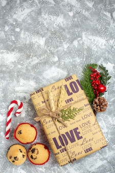 Overhead view of beautiful christmas packed gift with love inscription small cupcakes candy and fir branches decoration accessories conifer cone on ice surface