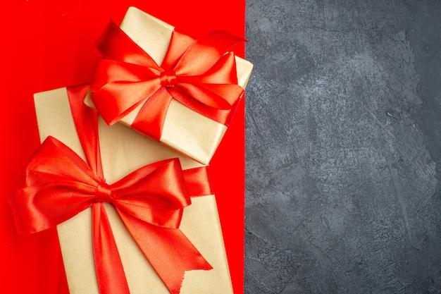 Vista dall'alto di bellissimi doni con nastro a forma di fiocco su sfondo rosso e nero