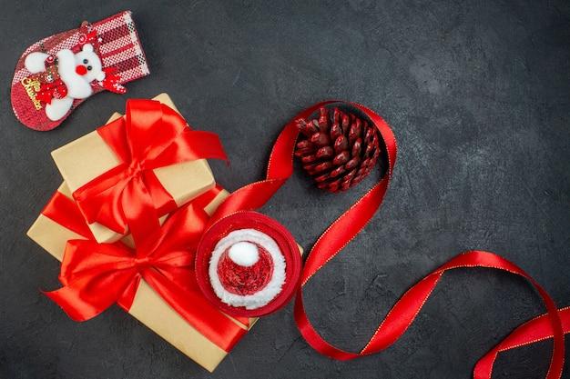 Vista dall'alto di bellissimi doni con nastro rosso e calzino di natale cono di conifere cappello di babbo natale sul tavolo scuro
