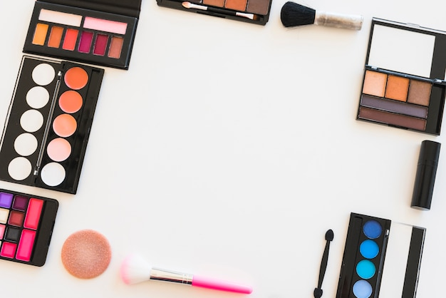 Overhead view of beauty products for professional make-up over white background