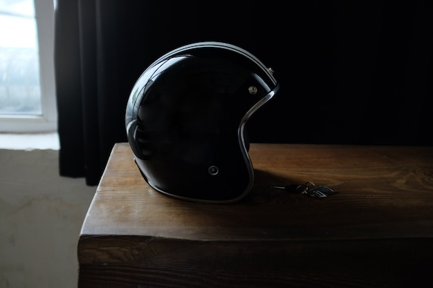 Overhead view of biker accessories placed on rustic wooden table.