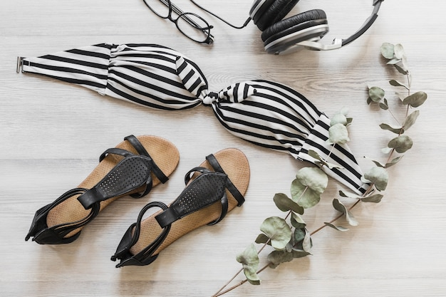 Overhead view of bikini top and footwear on the table