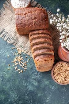 Vista dall'alto di pane nero fette di farina in una ciotola e grano su un asciugamano di colore nudo e vasi di fiori su sfondo di colori misti