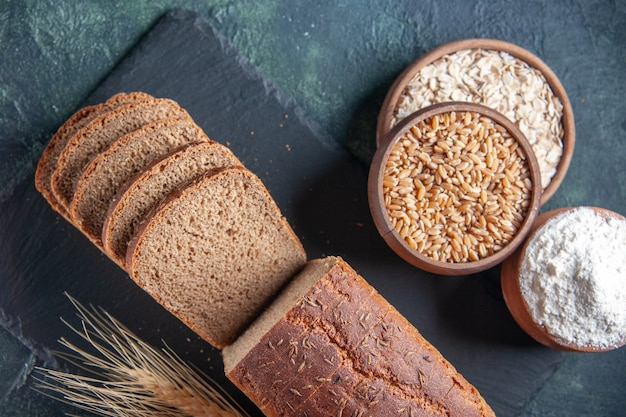 Vista dall'alto di fette di pane nero farina di farina d'avena grano saraceno su tavola di colore scuro su sfondo blu in difficoltà