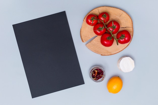 Overhead view of black slate with tasty tomato; dried chili; and lemon