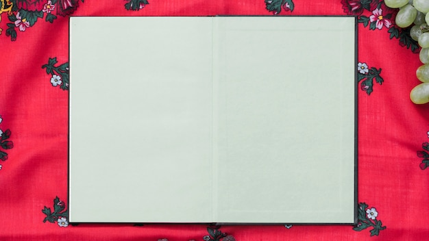 An overhead view of blank notebook on tablecloth