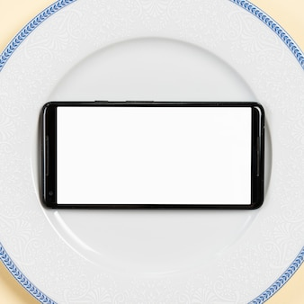 An overhead view of blank screen mobile on white plate