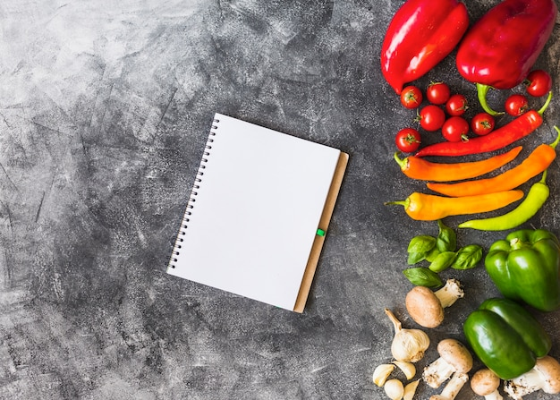 An overhead view of blank spiral notebook with colorful vegetables on rough background