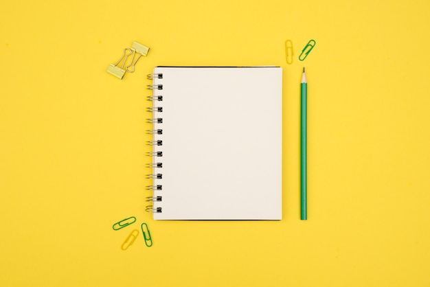 Overhead view of blank spiral notepad with pencil and paperclip over yellow surface