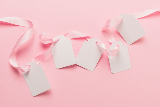 Overhead view of blank tags and pink ribbon against plain pink backdrop