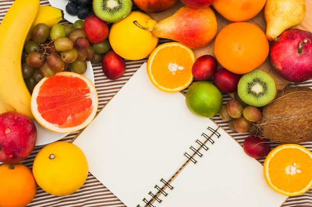 An overhead view of blank white spiral notepad with many colorful fruits