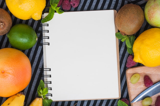 An overhead view of blank white spiral notepad with various fresh fruits