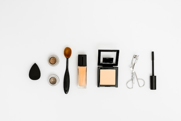 An overhead view of blender; eyeshadow; oval brush; compact powder; eyelash curler and mascara brush on white backdrop