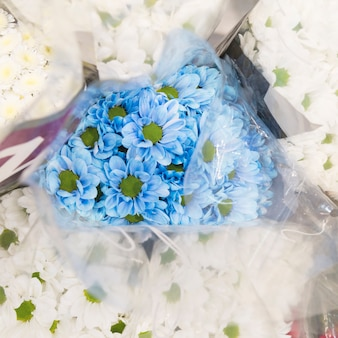 An overhead view of blue chamomile bouquet surrounded with white flower