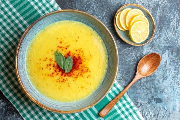 Vista dall'alto di una pentola blu con una gustosa zuppa servita con menta e pepe accanto a un cucchiaio di legno di limone tritato su sfondo blu