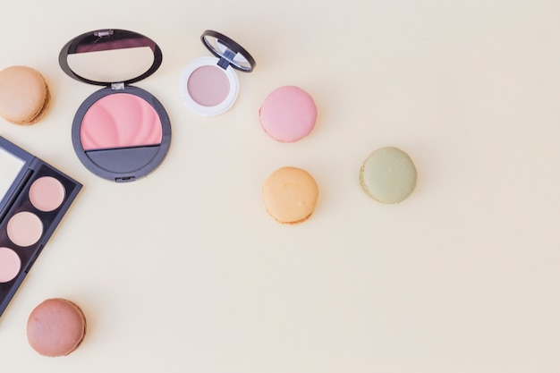 An overhead view of blusher and eyeshadow with macaroons on colored background