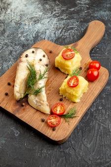 Vista dall'alto della farina di grano saraceno di pesce bollito servita con pomodori formaggio verde su tagliere di legno sulla superficie del ghiaccio