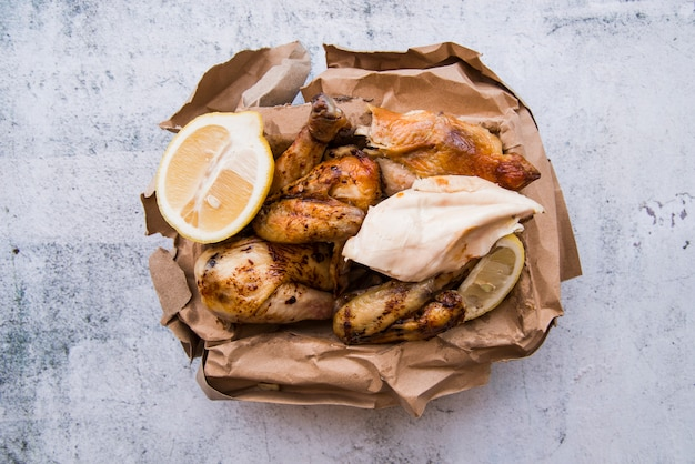Overhead view of boiled and roasted chicken with lemon in brown paper over concrete background