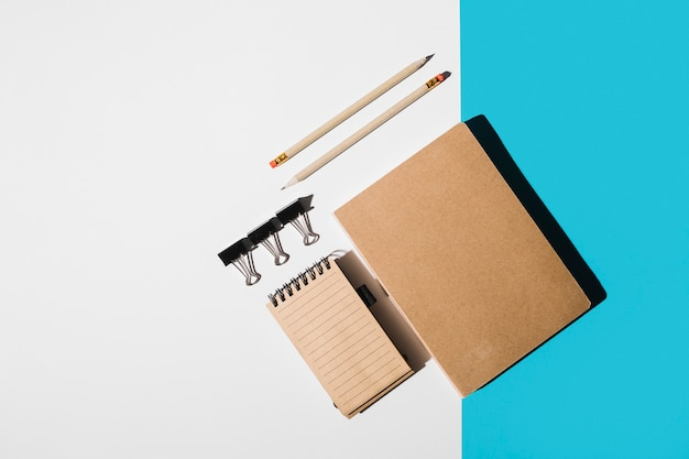 An overhead view of book; spiral notepad; pencil; bulldog clips on white and blue backdrop