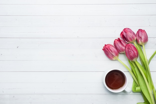 Overhead view of a bouquet of tulips and a cup of coffee. copy space. flat lay, top view