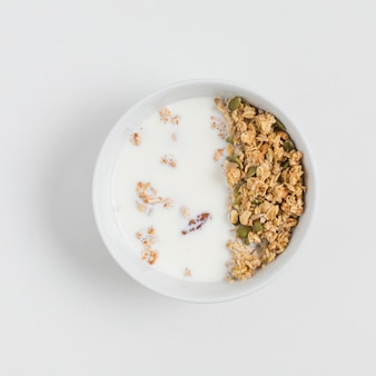 An overhead view of bowl with oats; milk and pumpkin seeds over white background