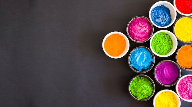 An overhead view of bowls with color holi powder on black backdrop