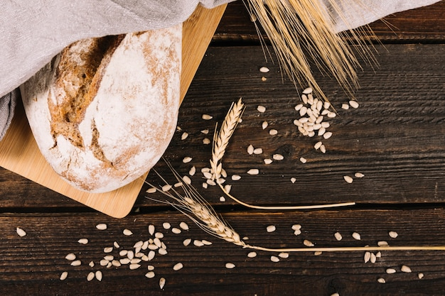 An overhead view of bread and ear of wheat with sunflower seeds on wooden table