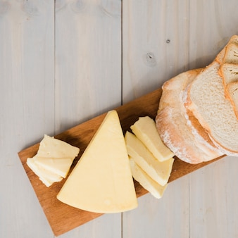 An overhead view of bread slices with cheese wedges on chopping board over wooden table