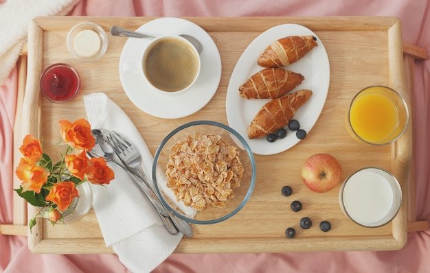 Overhead view breakfast served in bed on wooden tray Premium Photo