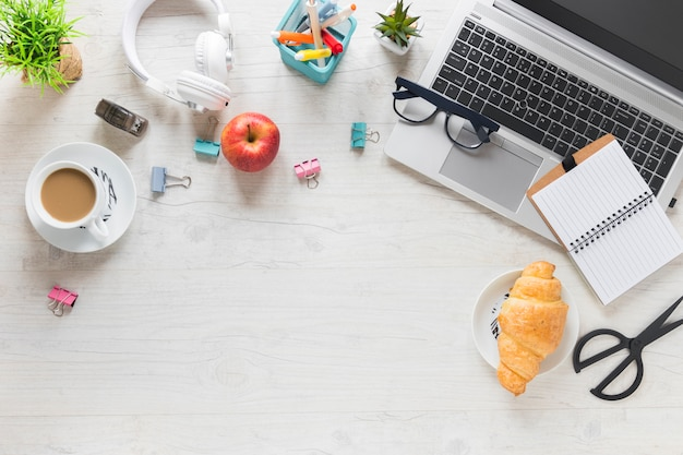 An overhead view of breakfast with office supplies and laptop on wooden desk