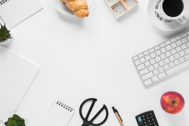 An overhead view of breakfast with office supplies on white desk