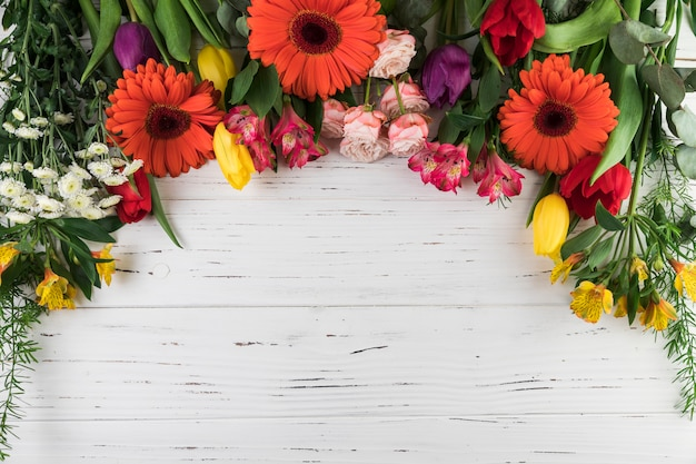 An overhead view of bright colored flowers on white wooden table