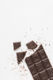 An overhead view of broken chocolate bar on white background