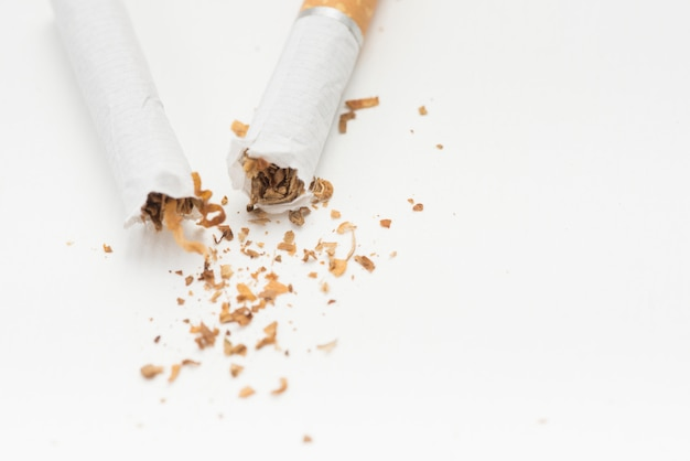 Overhead view of broken cigarette on white surface