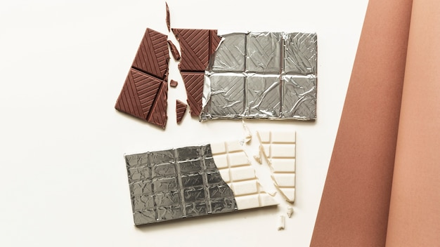 An overhead view of broken white and brown chocolate bar against white background