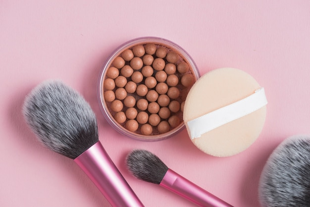 Overhead view of bronzing pearls; sponge and makeup brushes on pink backdrop