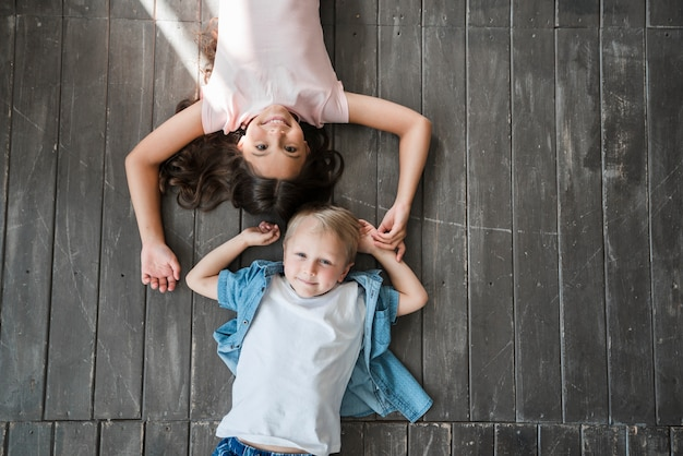 An overhead view of brother and sister lying on hardwood floor looking up