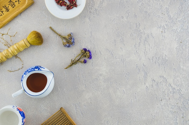 An overhead view of brush with herbal tea on concrete texture background