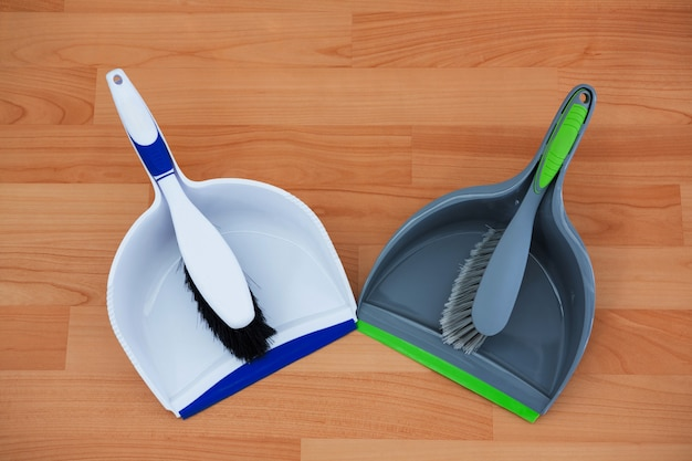Overhead view of brushs with dustpans on hardwood floor