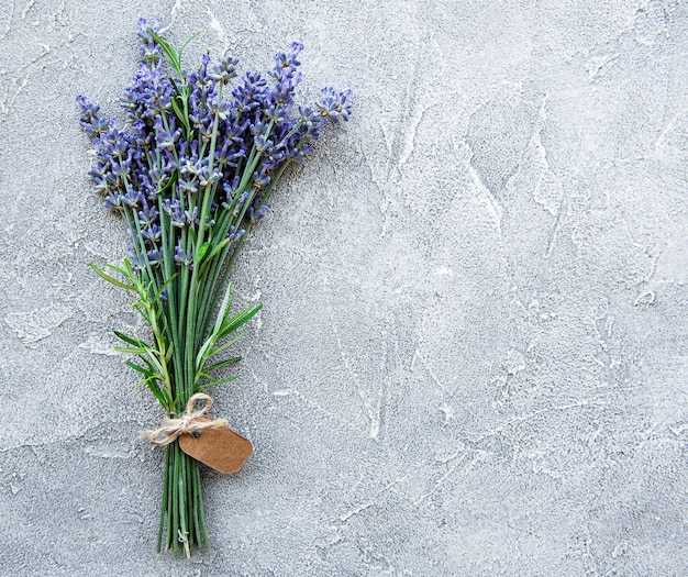 Overhead view of a bundle of fresh lavender flowers with blank tag over a concrete surface