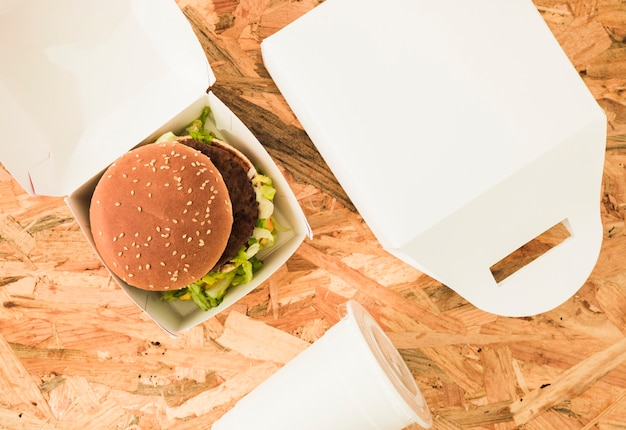 An overhead view of burger in package over the wooden background