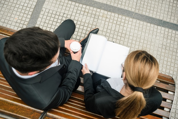 An overhead view of businessman and businesswoman sitting on bench reading document