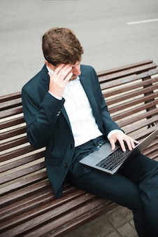An overhead view of a businessman sitting on bench at street using laptop
