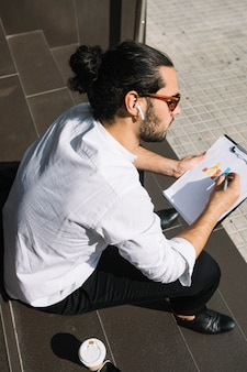 An overhead view of a businessman sitting on staircase drawing graph on clipboard