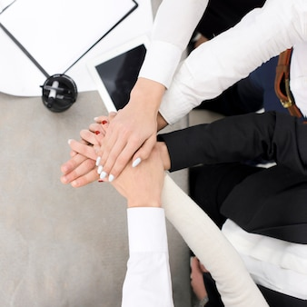 An overhead view of businesspeople stacking each other's hand over the desk
