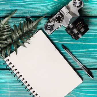 An overhead view of camera; fern; pen and blank spiral notepad on wooden textured background
